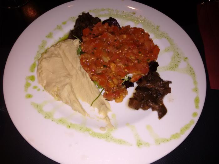 Ensalada de humus con berenjena escabechada, tomate especiado y aceite de sésamo