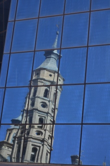 Torre de la Iglesia de San Juan de los Panetes refeljada en los cristales del parking